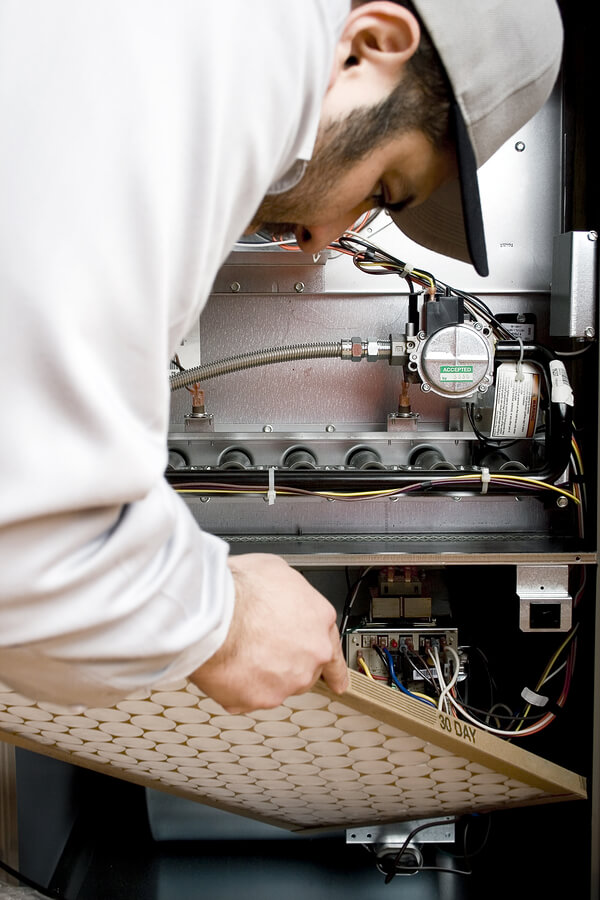HVAC technician replacing filter on furnace